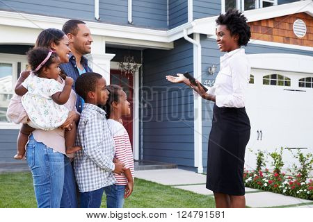 Real estate agent showing a family a house, closer in