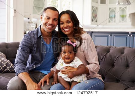 Happy parents with a baby girl sitting on mumâ??s knee