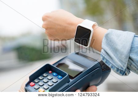 Woman using smart watch to checkout