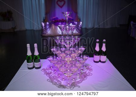 martini glasses in the form of a cascade or pyramid lit light at the wedding party