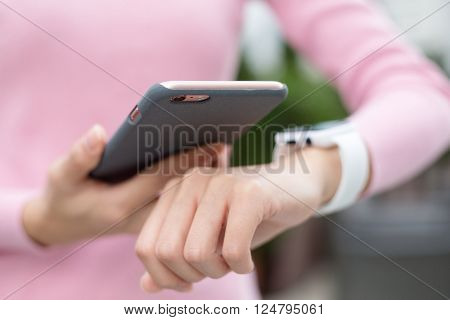Woman using mobile phone and watch
