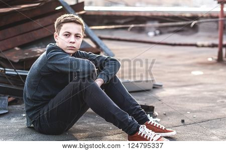 Lonely teenager sitting on roof the house