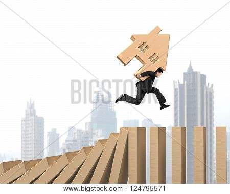 Man Carrying Wooden House Running On Falling Wood Dominos