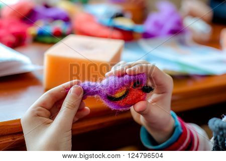 Manufacturing process from wool soft toys. Felting activity. The child makes a toy made of wool