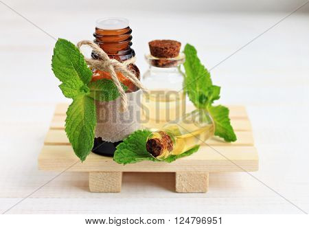 Essential mint oil in bottles, mint herb.