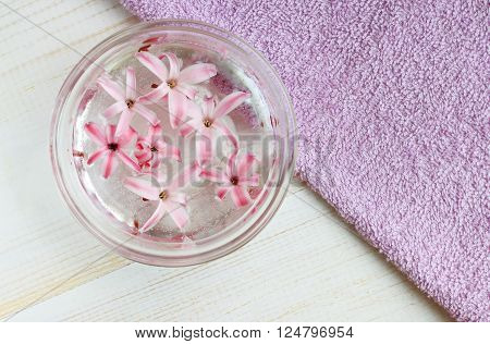 Aroma water. Hyacinth flower essence in bowl. Hand bath spa.