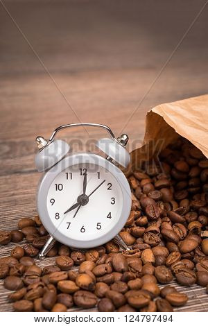 vintage alarm clock and coffee beans on wooden table
