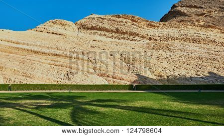 Beautiful lawn and well kept hedge with a textured layered rock face / mountain in the background