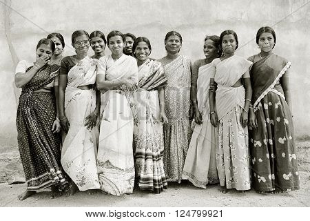 TAMIL NADU INDIA - May 16 1992: Indian women wearing saris at a village orphanage laugh and smile for a group portrait on May 16 1992 in Nagercoil Tamil Nadu India.