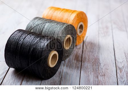 black gray orange waxed thread for hand-stitching leather on a wooden background