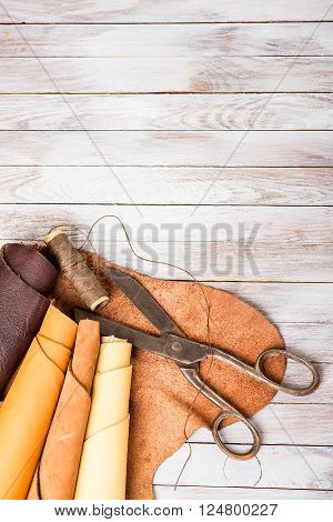skin rolls with scissors and thread on a wooden background