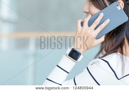 Woman talk to cellphone and wearing smartwatch