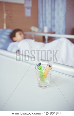 Syringes in a glass measuring cup with blurred illness boy lying on sickbed in hospital. Syringe in focus, child out of focus. Health care and medical concept. Vintage style.