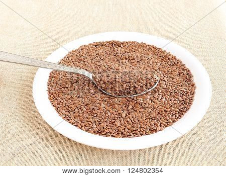 Healthy food flax seeds in a steel spoon.
