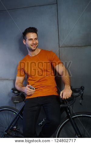 Happy young man leaning against bicycle, holding mobilephone, looking away.