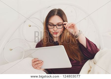 Young woman reads from tablet pc in bed. Girl in eyeglasses looks into gadget tablet pc. Beautiful woman in nightwear at bed in morning surfing internet at her tablet computer. High key. Soft toning