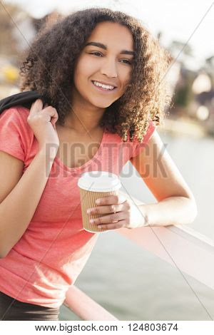 Beautiful happy mixed race African American girl teenager female young woman with perfect teeth smiling drinking takeaway coffee outside