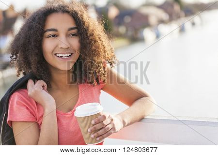 Beautiful happy mixed race African American girl teenager female young woman smiling drinking takeaway coffee outside on a bridge
