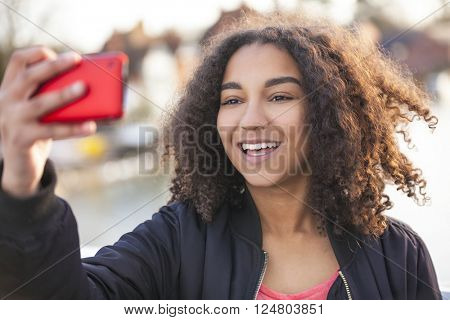 Beautiful happy mixed race African American young woman girl teenager female child smiling with perfect teeth taking selfie photograph with red cell phone