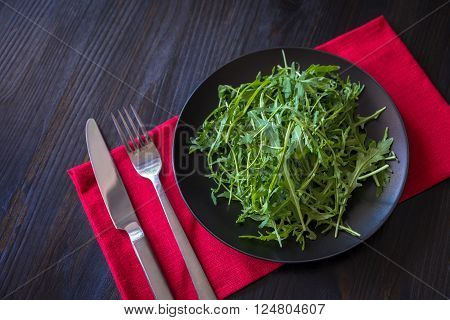 fresh rucola leaves on black plate and wood background
