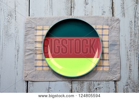 Empty plate with German flag on light blue wooden background