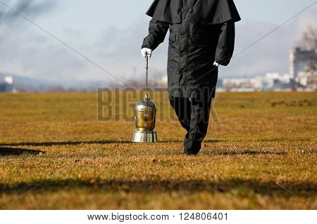 Funeral director undertaker carrying an extravagant urn with ashes of a cremated human during a formal scattering ceremony. Death cremation funeral Day of the dead concept.
