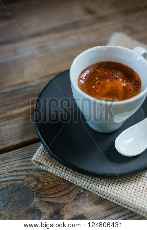 White cup of espresso crema with black saucer, stack of dark chocolate bar on old wooden table. Cup of Espresso - stock photo.