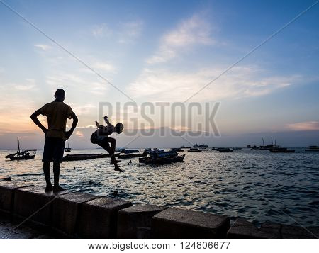 STONE TOWN ZANZIBAR - MARCH 28 2016: Local boys jumping to the water in the early evening in Waterfront Stone Town Zanzibar. Horizontal orientation.