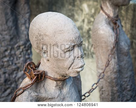 STONE TOWN, ZANZIBAR - MARCH 28, 2016: Sculpture of slaves dedicated to victims of slavery in Stone Town of Zanzibar placed close to the former slave market.