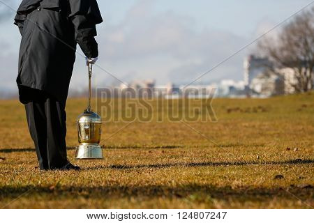 Funeral director, undertaker, starting to scatter ashes of a cremated human on a designated field for ash scattering. Death, cremation, funeral, Day of the dead concept.