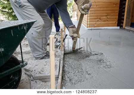 Masons filling wood form with a shovel of concrete mix for floor base in front of the house. Construction business and tools do-it-yourself basic work around the house concept.