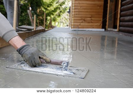 Mason leveling and screeding concrete floor base with square trowel in front of the house. Construction business do-it-yourself precision work around the house concept.