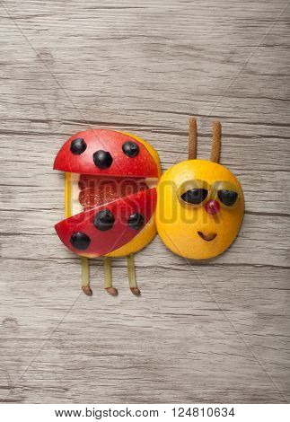 Ladybird made of fruits on wooden background