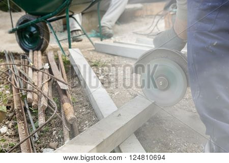 Construction worker cutting a reinforced concrete pillar for installation with coworker in the background resting. Construction business DIY dirty and dangerous work around the house concept.