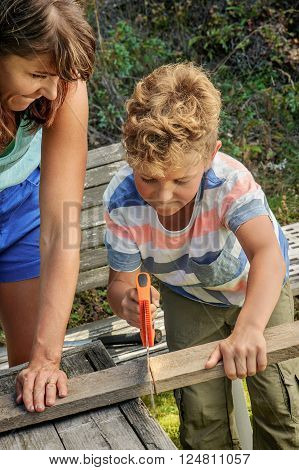 Mother teaches son how to use a saw. They're outside in the garden. Traditional man's role played by woman