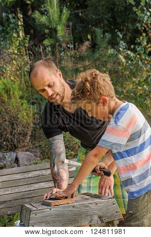 Father teaches son how to hammer a nail. He worries about getting his fingers hit. They're outdoors. The father has tattoos.