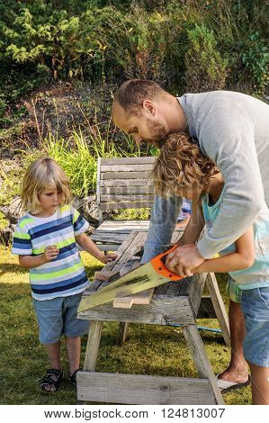 Father teaches his young sons how to saw a piece of wood. They're outdoors in a garden and use a wooden saw bench