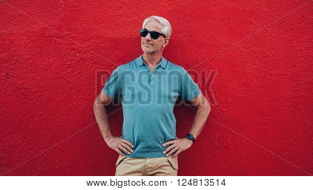 Portrait of handsome senior man standing with his hands on hips looking away at copy space against red background.