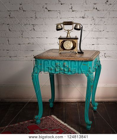 Retro composition of green vintage wooden table and old golden telephone set on a background of red carpet dark brown wooden floor and white bricks wall