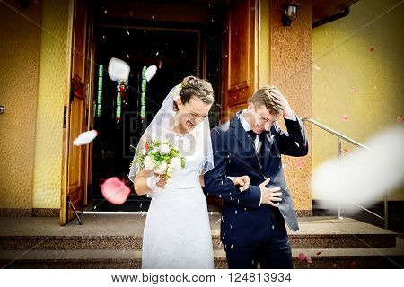 Newlyweds Coming Out Of The Church After Wedding Ceremony.
