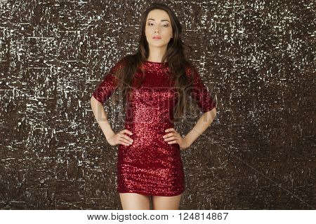 Studio portrait. Sexy young brunette woman in evening red dress