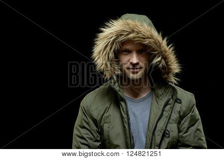 Low key studio portrait of young adult confident caucasian model wearing winter coat with hood on and smirking. Isolated on black.