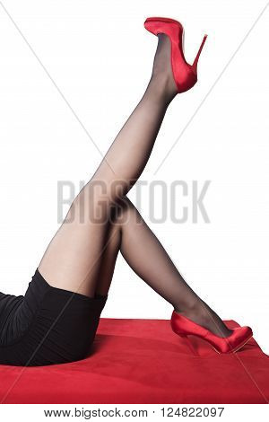 female lying on a red sofa with one leg up in the air wearing red heels on white background
