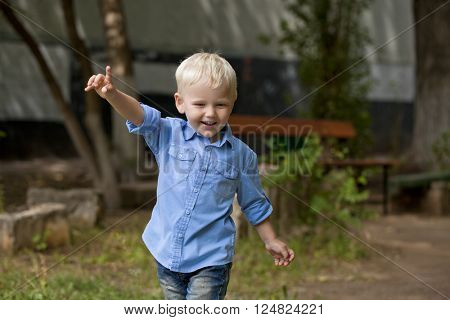 Portrait of blonde baby boy in summer street, outdoors