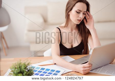Tired after work. Pleasant beautiful exhausted woman sitting at the table and feeling gloomy while using laptop