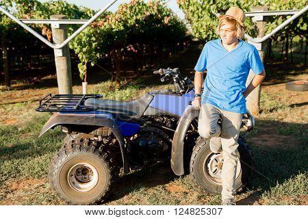 Boy standing next to truck in vineyard