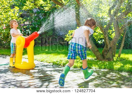 Two funny little kid boys playing together and splashing with a garden hose on hot and sunny summer day. Twins having fun outdoors. Funny outdoors leisure wth water for children.