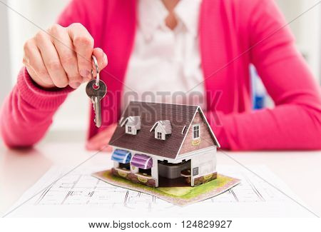 Female house agent holding keyring of rented house.