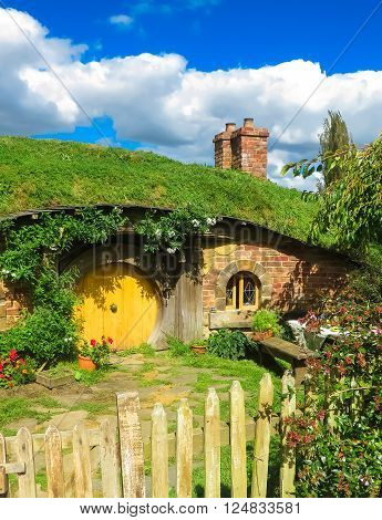Hobbiton Film Set, New Zealand - March 31, 2015: A hobbit home in Hobbiton in Matamata, showing a yellow door, chimney and a fence