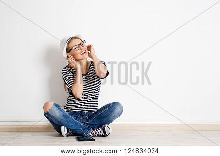 Young modern woman sitting on empty floor with ipad and singing songs. Portrait of funny girl with tablet pc and headset. Teenage lifestyle concept.